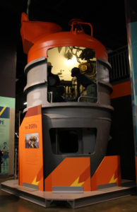 Image of a gray submarine rescue chamber with red top. Openings have been cut into one side of the chamber to show the interior components. Mannequins are staged inside the chamber.