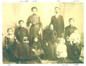 A family photograph from 1909 of five adults and four children