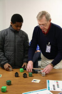 Image shows museum volunteer engaging a young learner with programmable cubes during an education program.