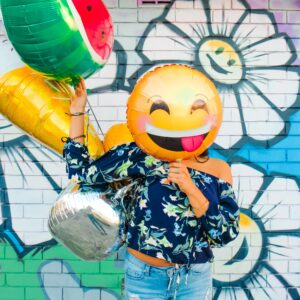 Creative Woman holding a funny emoji face balloon in front of her face