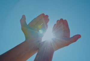 Hands in Sky With Beam of Light
