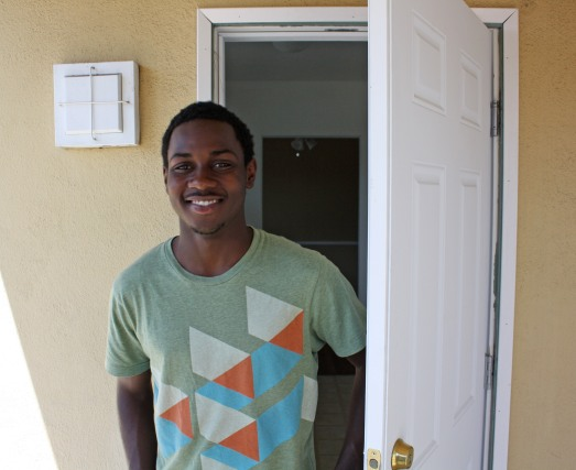 Photo: Sheldon, a young black man, stands smiling in an open doorway.