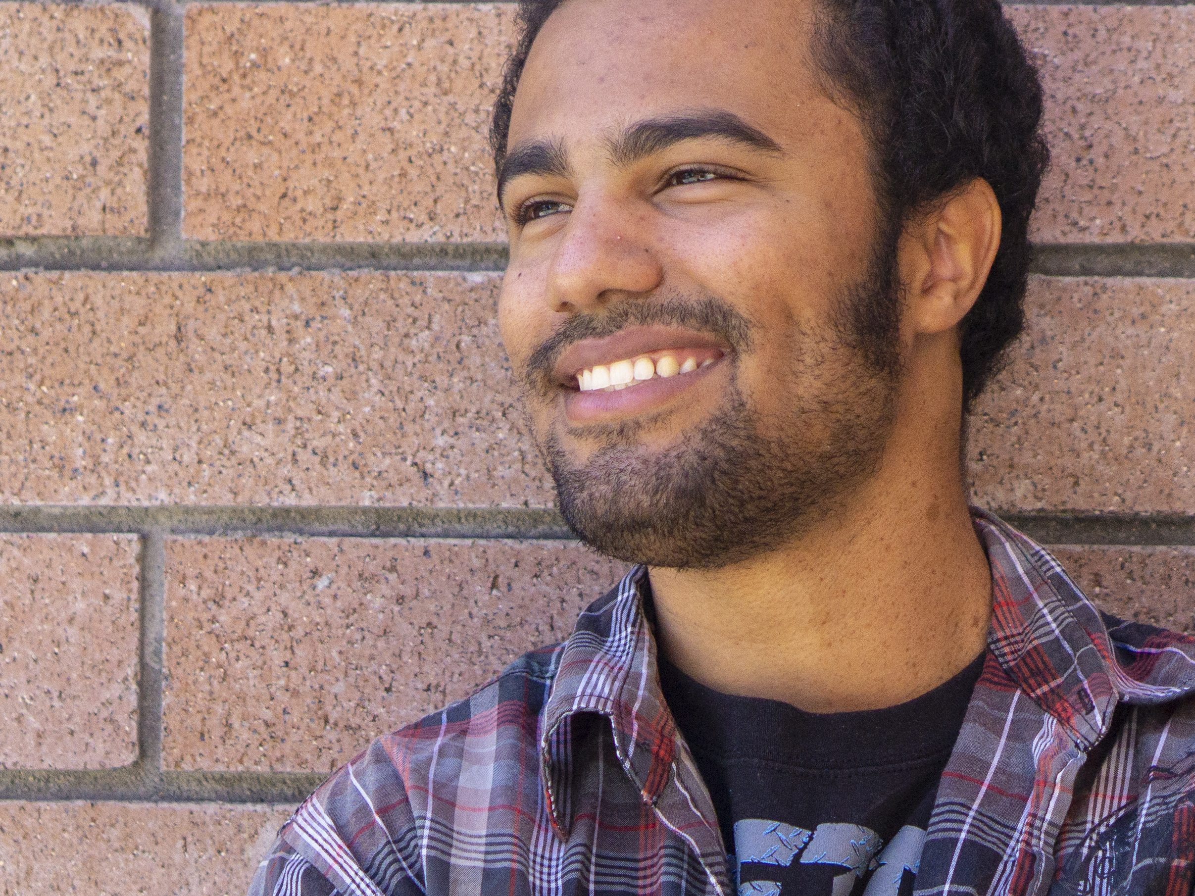 Close-up portrait of Fearious, a young black man, standing in front of an orange brick wall and smiling