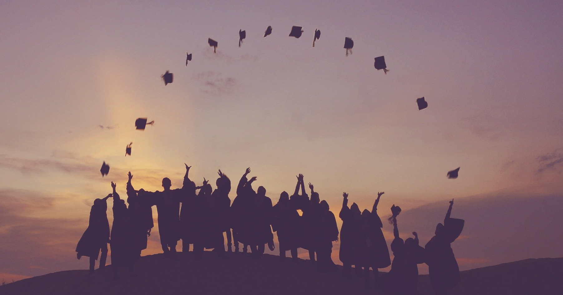 Stock photo: in early morning light, the silhouette of a group of graduates standing in a line throwing their caps into the air