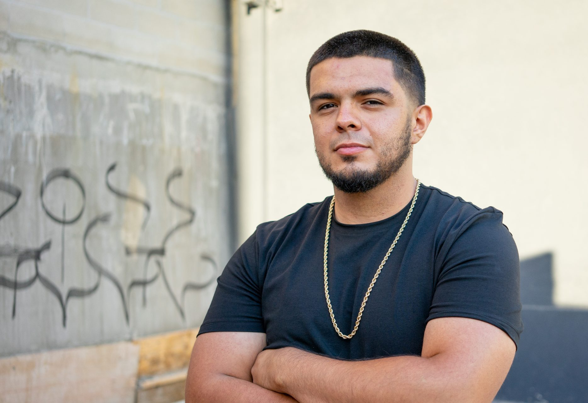 The Big Picture: Sergio, a young latino man with his arms crossed, looks at the camera