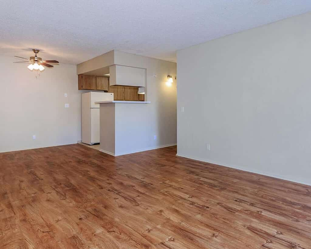 Empty living room with view into kitchen