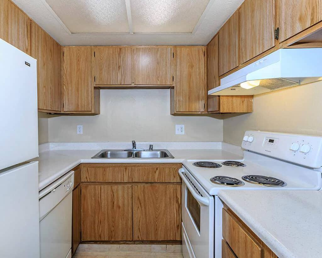 Kitchen area with wood cabinets and white countertops and appliances