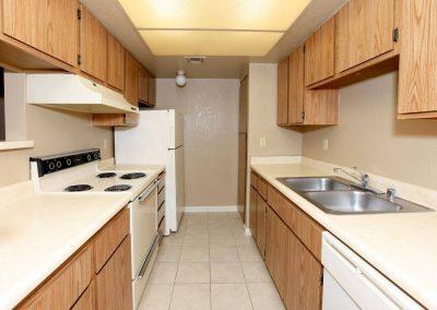Kitchen with sink, cabinets, fridge, dishwasher, stove, oven and range fan
