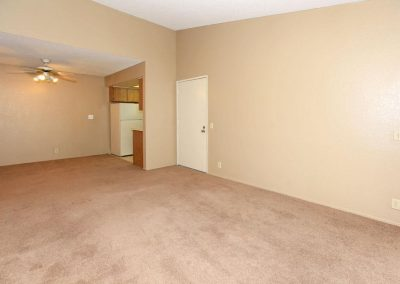 Two bedroom one bathroom living area with carpeted floor, ceiling fan, entry to kitchen