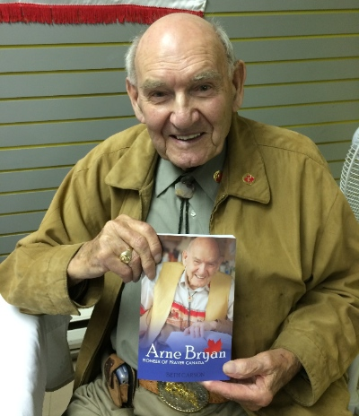 Arne Bryan holding the story of his life. Photo by Rev. Ed Hird.