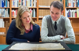 UBC's Katherine Kalsbeek and Richard Pollard admire the Papal bull acquired by UBC Library. The document was written in 1245. Credit: Don Erhardt