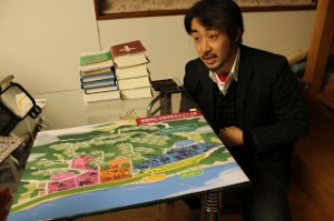Pastor Ikarashi with a proposed new community design for Usuiso.