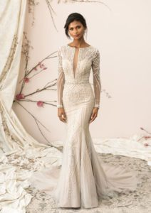 Your wedding day look will never be forgotten with this opulent beadwork that covers the sleeves, bodice and skirt of the gown. Lined with innovative stretch mesh. The hand beaded Sabrina neckline with plunging V-neck matches the illusion back adorned with beading and working button closures.