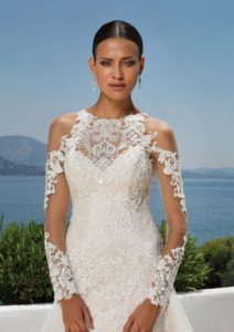 Your attention to style is evident in this cold shoulder, jewel neckline gown. Embroidered lace accents the illusion sleeves with button and loop closures at the wrist. Stretch lining is used to create an impeccable shape for the fit and flare silhouette. For added drama a detachable tulle skirt attaches at the bottom of the deep illusion back.