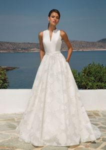 Feel elegant with this structured sleeveless mikado ball gown with structured notch collar. The organza Jacquard fabric is gathered for added volume and has pockets and a classy high-back finished with covered buttons.