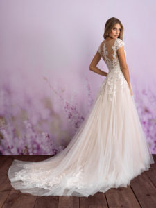 Romantic and timeless, this tulle gown features illusion cap sleeves and a striking train.