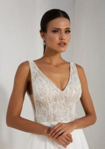 Dainty pearl and rhinestone beading lies atop a sheer Chantilly lace bodice with a low V-neckline found on the front and the back. Paired perfectly with a circular cut chiffon skirt, movement is limitless