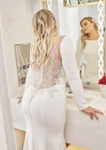 Turn heads with this crepe long sleeve fit and flare gown lined with Jersey from top to bottom. An elaborately beaded motif on the sheer illusion back shows that the beauty is all in the details.