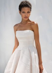 Allover geometric organza trim adorns this strapless ball gown with a cathedral length train creating a timeless wedding day look.