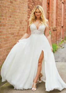 Movement is limitless in this flowy A-line gown featuring beaded spaghetti straps. Hand beaded appliques adorn the illusion bodice that then leads to a clean tulle skirt with a slit. Also available lined or without the skirt slit for a more conservative look.