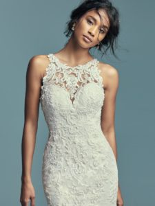 Classic yet striking, this fit-and-flare wedding dress features beaded lace motifs, crosshatch details, and Swarovski crystals over tulle. Lace motifs adorn the illusion halter over sweetheart neckline and illusion back. An illusion double-lace train completed the elegant romance of this look. Finished with covered buttons over zipper closure.