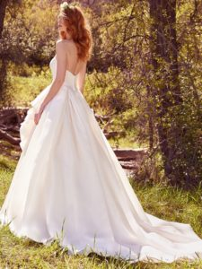 xMade of Shavon organza, this simple yet striking ballgown wedding dress features handmade rosettes accented with pearls. A strapless scoop neckline and flowing train evoke chic romance. Finished with covered buttons over zipper and inner elastic closure.