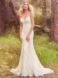 Lace appliqués cascade down the bodice, breathtaking scalloped hem, and illusion open-back in this tulle over Vogue satin wedding dress. Featuring beaded spaghetti straps, a V-neckline, and beaded embellishments in a fit-and-flare silhouette. Finished with covered buttons over zipper closure.