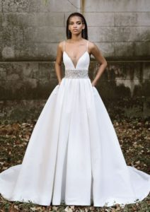 A cutting edge style with a deep, plunging neckline with beautiful and hand beaded waistband. Couture knife pleats accent the mikado natural waist and added pockets highlight this stunning ball gown.