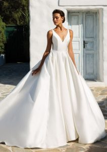 This look embodies the new clean trend with a structured Mikado V-neckline with couture seaming at the waist. Box pleats create volume and the hand beaded illusion back adds a unique element of surprise. The dress is finished with a cathedral-length train, but a chapel-length train is also available.