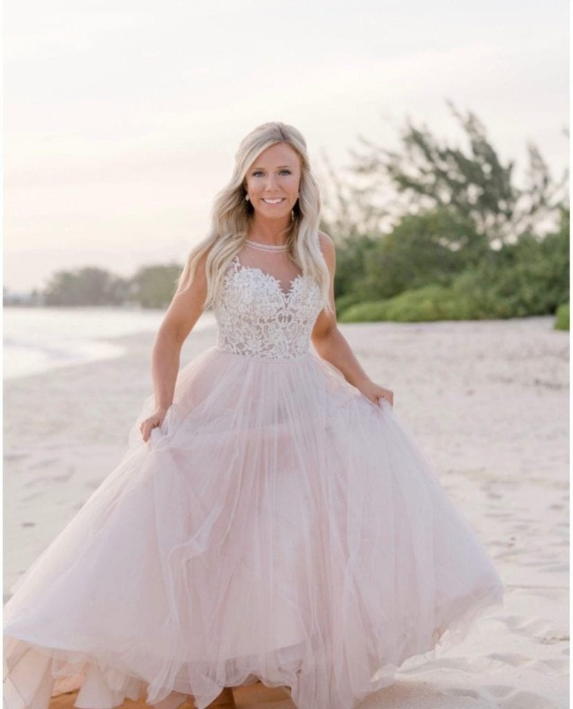Gorgeous bride on the beach in a blush ball gown with lace.