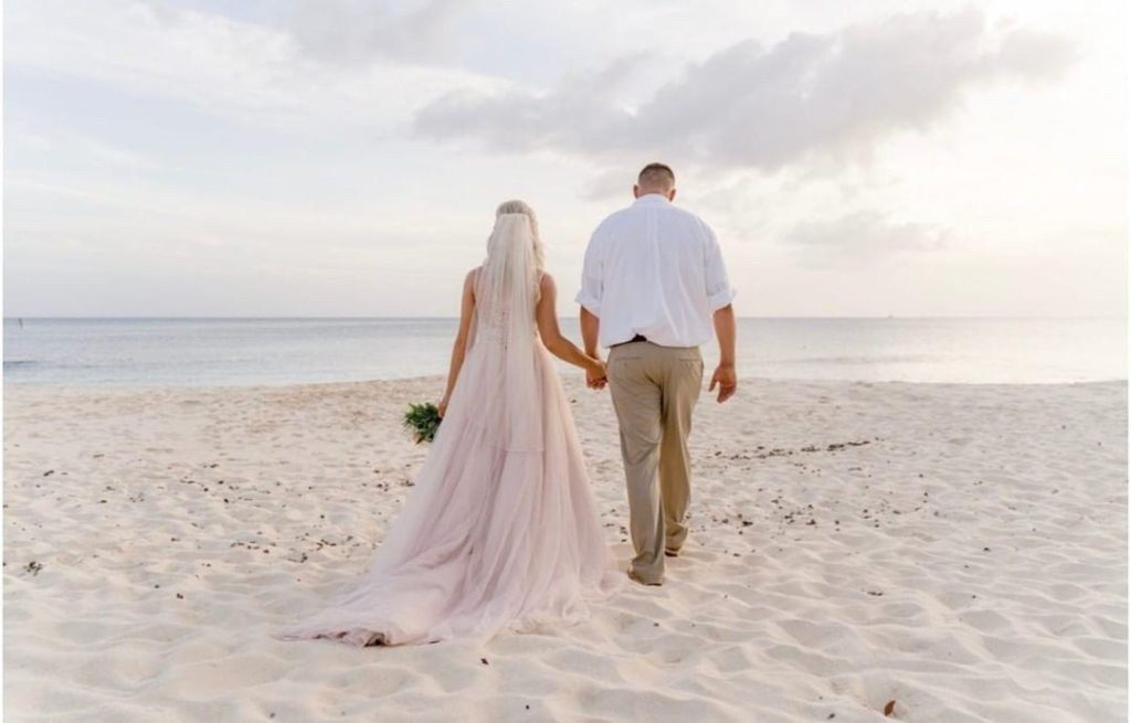 Bride and groom on their wedding day. Destination wedding in Grand Cayman.  On the beach.  Blush ball gown long flowing veil.