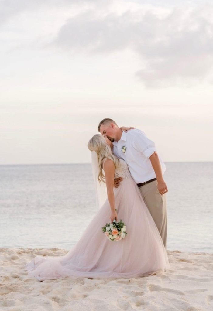 Destination wedding day bride and groom kissing on the beach.  Beautiful blush ball gown with long flowing veil for the bride.