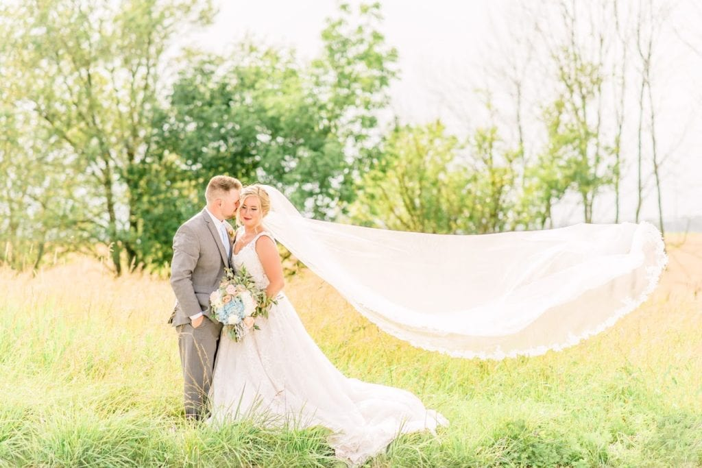 Bride and groom in field on wedding day with veil flying in the wind.  Bride in Allure Couture ball gown and groom in light grey tuxedo.