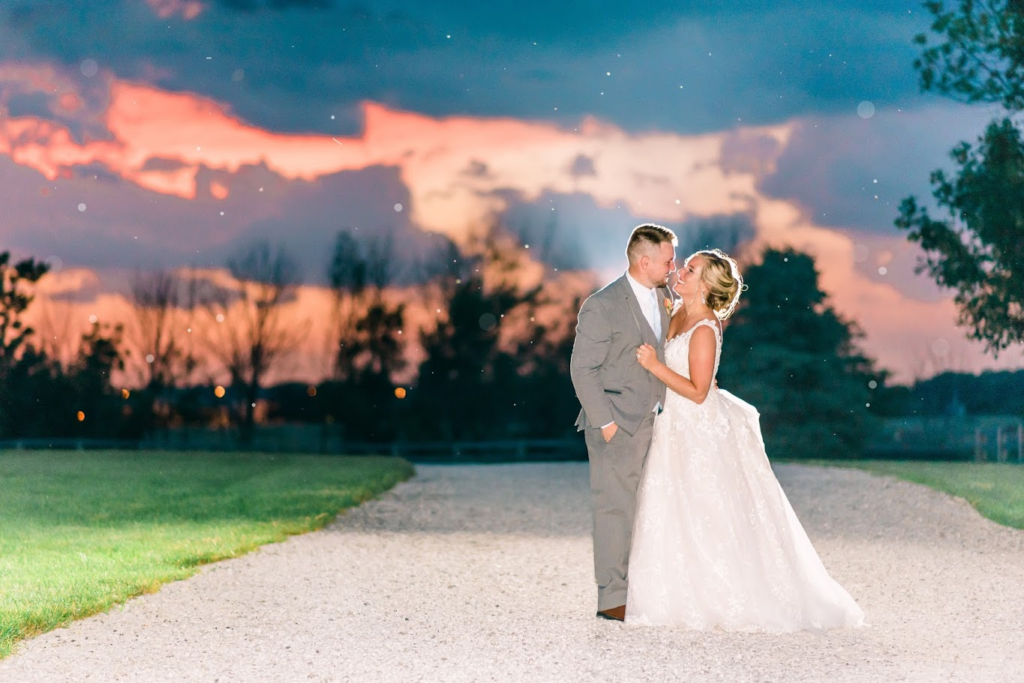 Bride and groom at sunset with gorgeous sky .  Bride in lace ball gown and groom in light grey tuxedo.