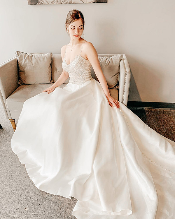 satin ball gown with beaded detail wedding dress bride sitting on couch