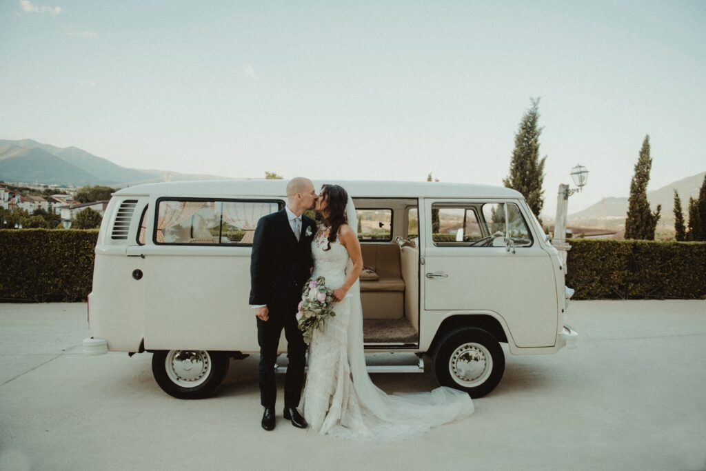 bride and groom kissing in front of VW van bride in lace strapless wedding dress