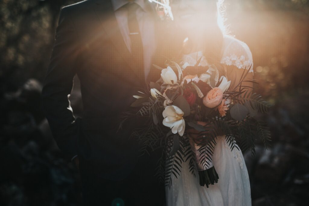 bride and groom at sunset getting married with flowers indiana wedding