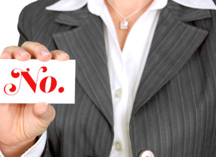 "lady holding business card that reads ""no"""