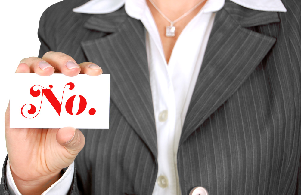 """lady holding business card that reads """"no"""""""