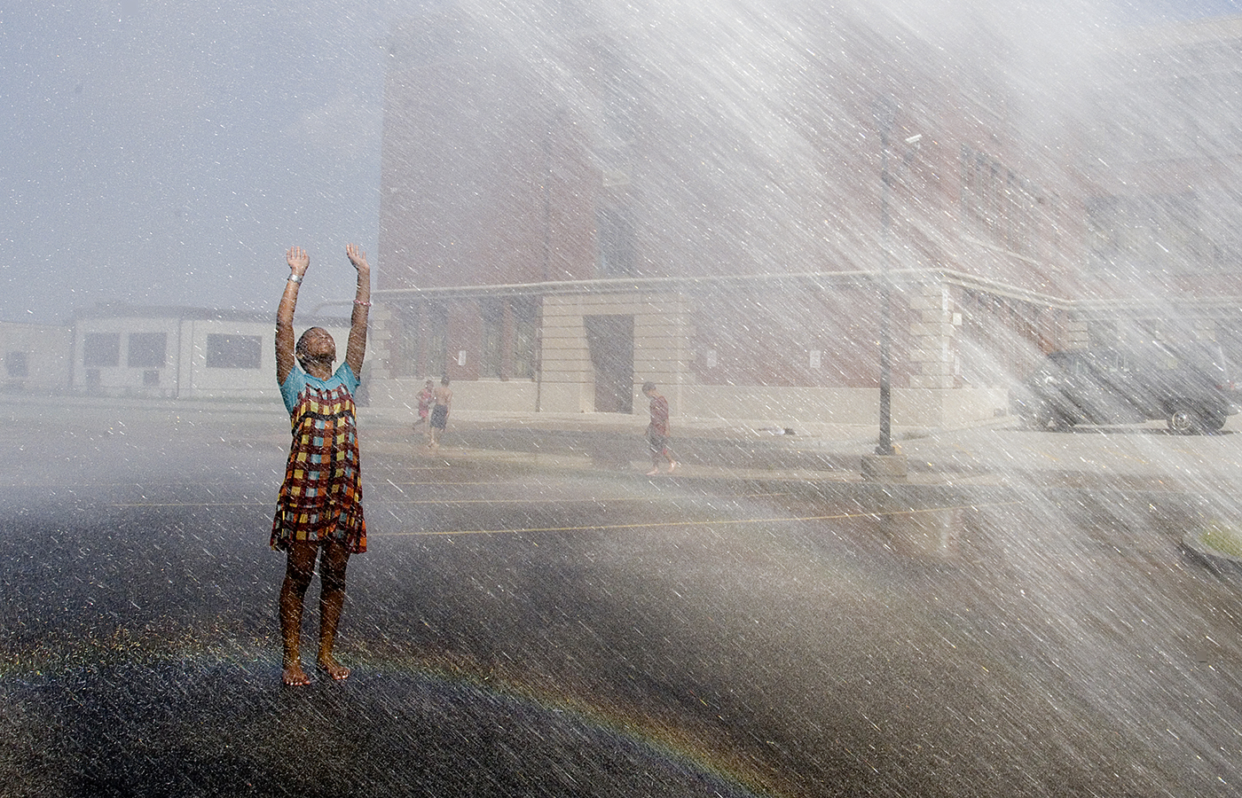 Ajanee Mohammed, 11, of Rochester, cool off in the spray from an open fire hydrant at School 41 on Ridge Road. The city opened hydrants and spray parks across the city to help residents cool off on a hot day. (staff photo by Jeffrey Blackwell)  (staff photo by Jeffrey Blackwell)