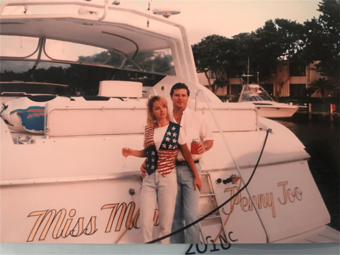 A couple taking a photo in front of a yacht