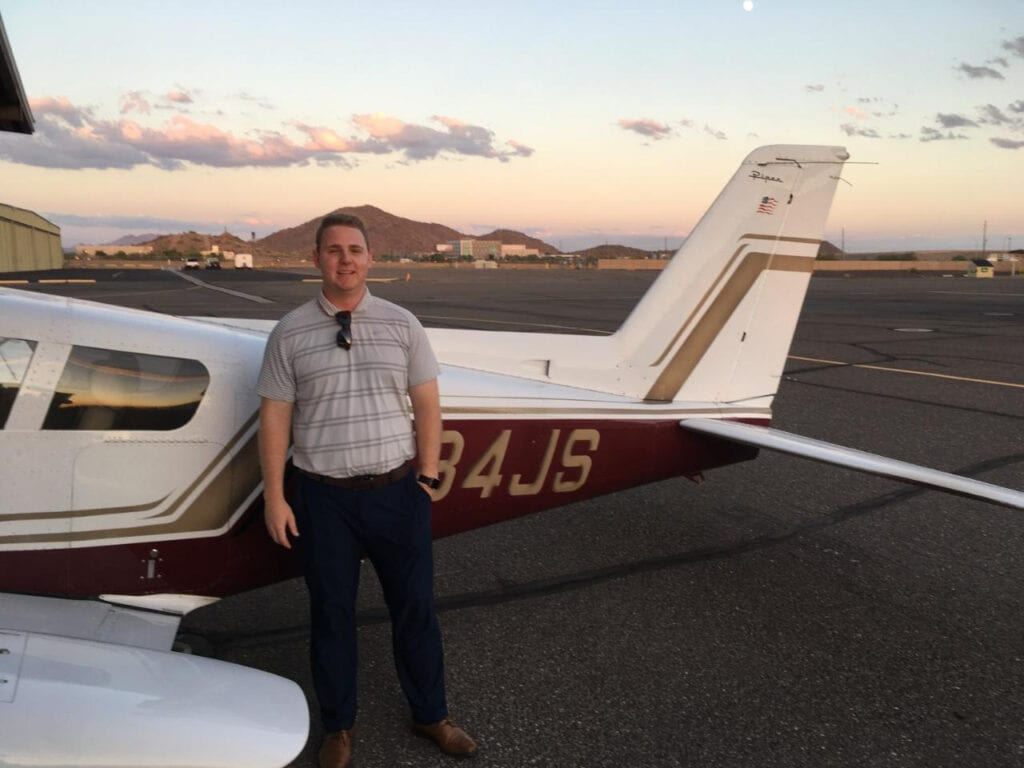 Man in a gray polo shirt next to a plane.