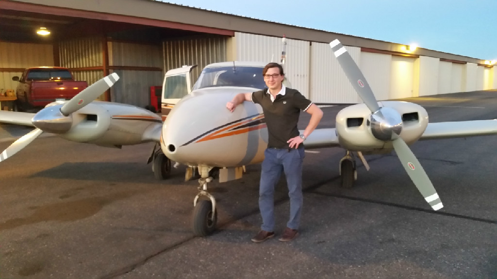 A young guy wearing glasses and black shirt standing next to a plane.