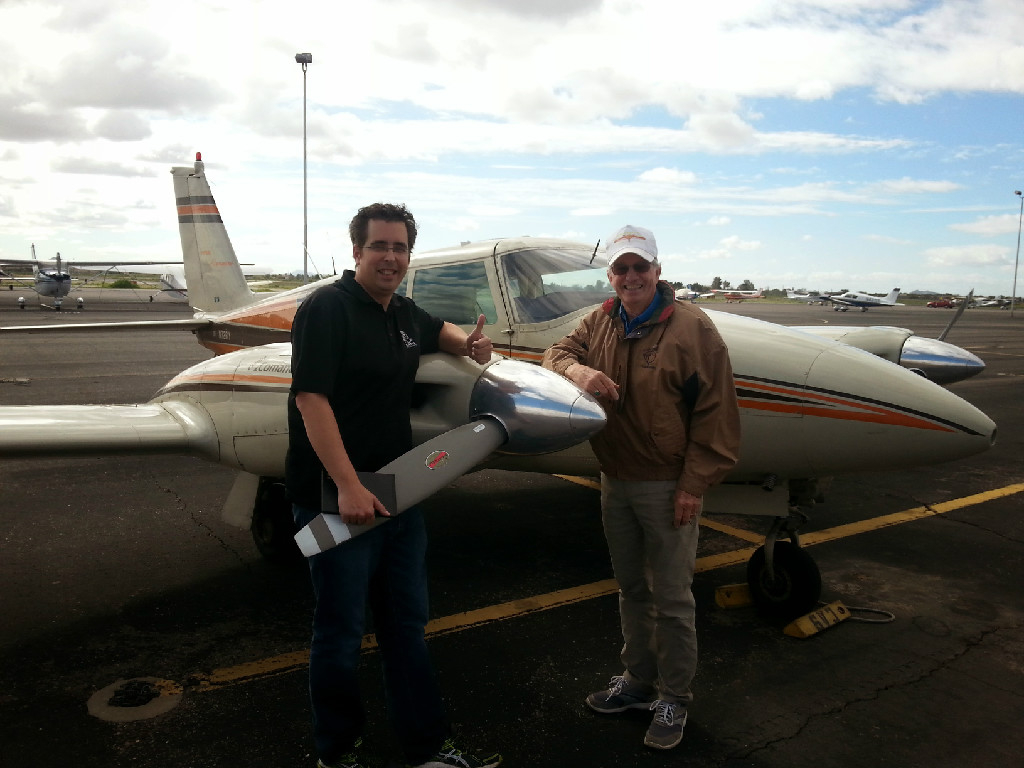 Two guys posing next to a plane's propeller.