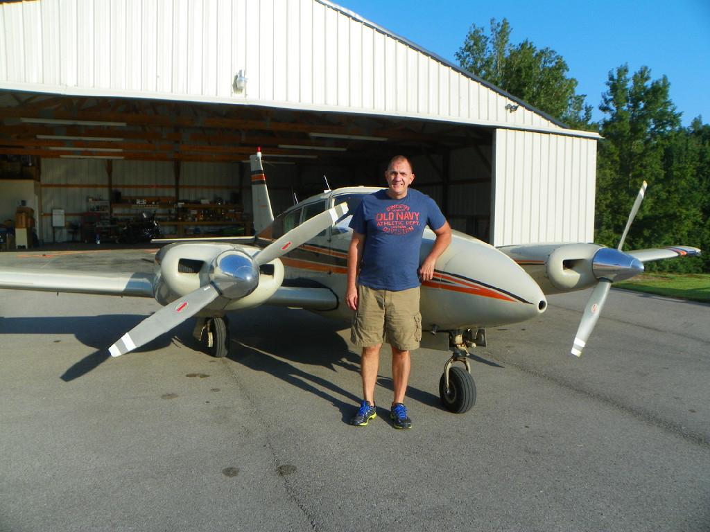 An old man wearing a dark blue shirt standing beside an aircraft.