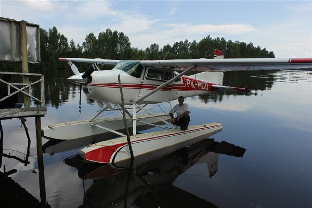 A man posing with a seaplane.