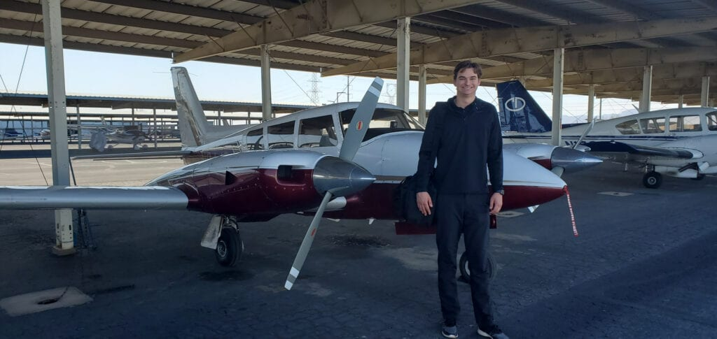 Man in a black sweater standing next to an airplane.