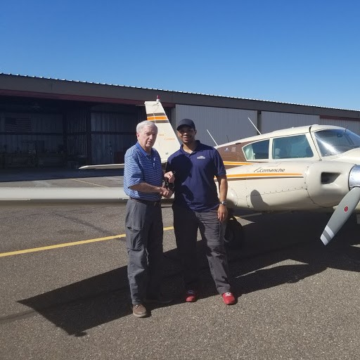 Two Caucasian men shaking hands in front of a Piper Twin Comanche.