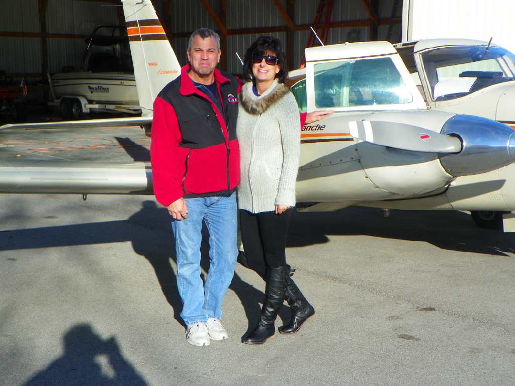 A man and a woman taking a photo beside an airplane.