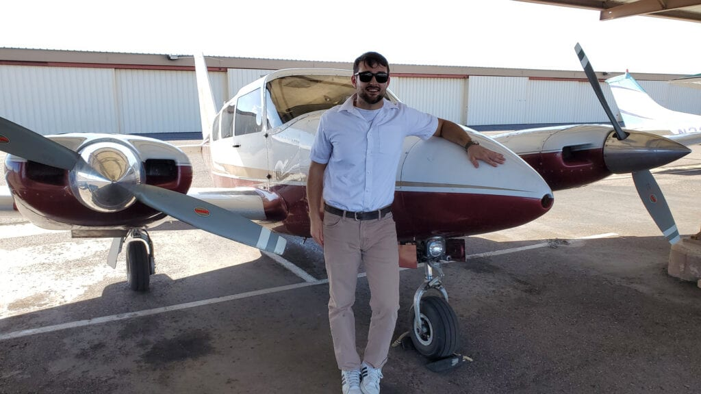 Man in a white shirt and khaki pants leaning on an aircraft.